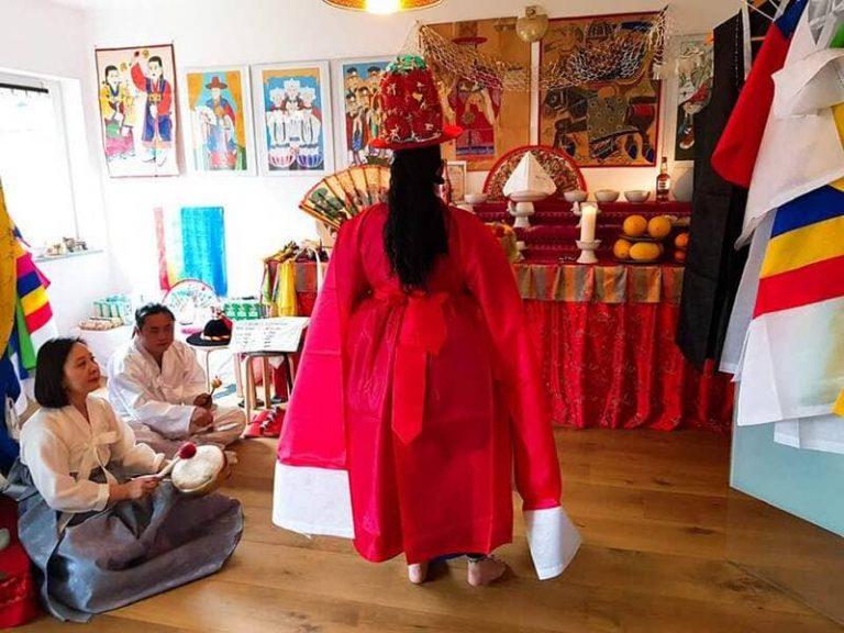 Ritual mit roter Götterkleidung vor dem Schamanenaltar