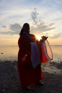 Sonnenuntergang Chiemsee Andrea Kalff mit Götterkleidung und Glocken