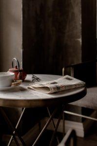 Zeitung auf dem Tisch mit Tasse Tee